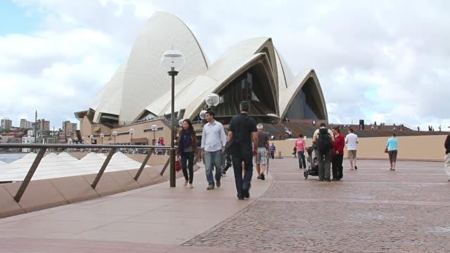 ms shot of  sydney opera house with people walking in area / sydney, australia - opernhaus stock-videos und b-roll-filmmaterial