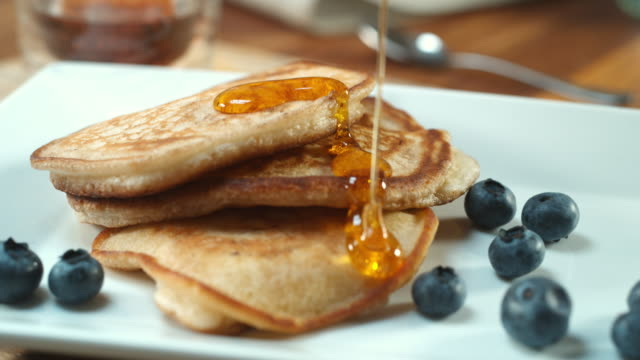 cu td slo mo shot of syrup being poured on to stack of pancakes / united kingdom - food stock videos & royalty-free footage