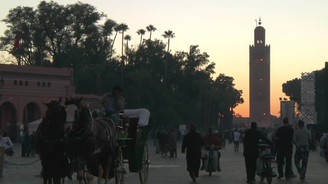 ms shot of tall monument building with people walking on street / marrakech, tensift, morocco  - wiese stock videos & royalty-free footage