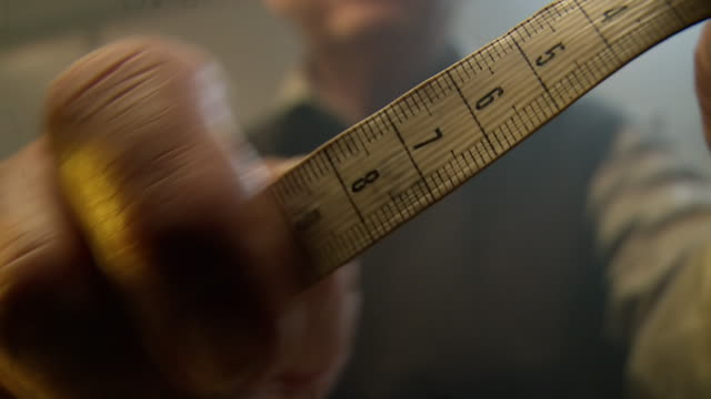 cu shot of tape measure being held by man / south africa - measuring stock videos & royalty-free footage