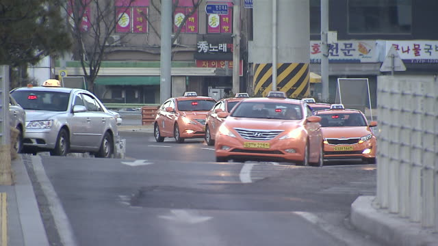ms shot of taxi coming down toward taxi stand / seoul, seoul, south korea - taxi stand stock videos and b-roll footage