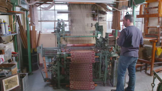 ms td shot of technician stands in front of a jacquard loom as it weaves a patterned fabric / red lion, pennsylvania, united states  - loom stock videos & royalty-free footage