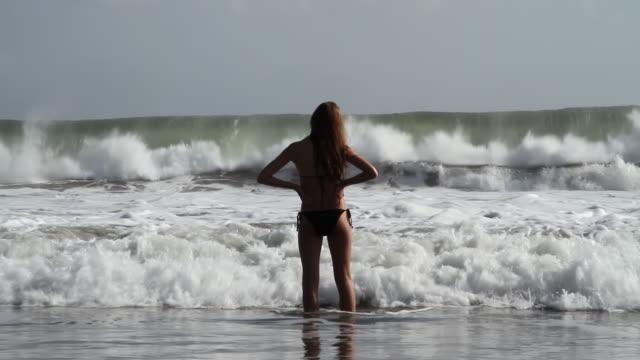 ms slo mo shot of teenage girl standing in sea waves / seminyak, bali, indonesia - only teenage girls stock videos & royalty-free footage