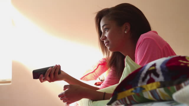 vídeos de stock, filmes e b-roll de ms shot of teenage girl watching television in her bedroom / lamy, new mexico, united states - reclinando