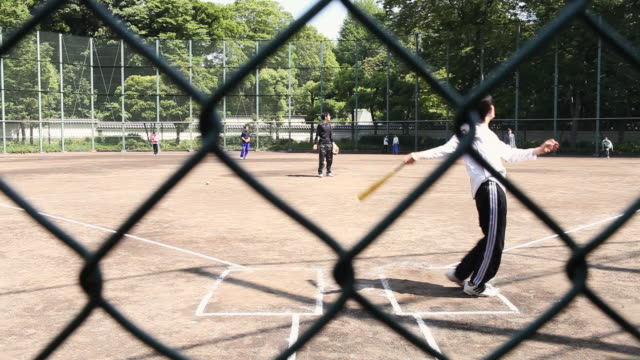 ms shot of teenagers playing baseball on public baseball field / tokyo, kanto, japan - hitting stock videos & royalty-free footage