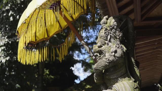 ms shot of temple guardian figure with temple umbrella at pura tirta empul / tampaksiring, bali, indonesia - ubud district stock videos & royalty-free footage
