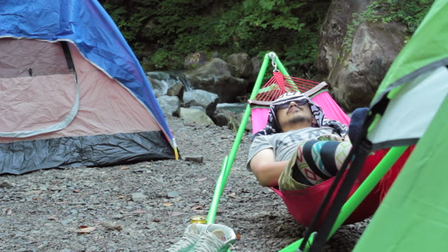 ms pan shot of tent and man resting / okutama, tokyo, japan - tent stock videos & royalty-free footage