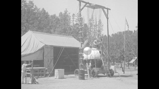 vídeos de stock e filmes b-roll de shot of tent camp / men on top of balloon gondola suspended from rack / closer shot of gondola with its door open / two shots of man inside gondola... - rapid city
