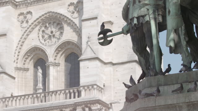 Shot of the 'Charlemagne et ses Leudes' statue with the western facade of Notre-Dame de Paris in the background in Paris, France