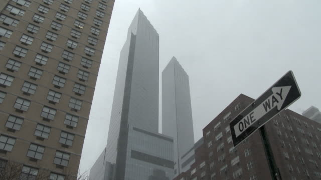 Shot of the Columbus Towers in New York City on a snowy day. A one way street sign in also visible in the shot
