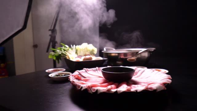 vídeos y material grabado en eventos de stock de 2 toma del concepto del estudio de producción de alimentos mientras filmaba el set de shabu shabu en la mesa. - plató de cine