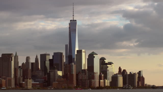 vídeos de stock, filmes e b-roll de shot of the downtown manhattan skyline from across the hudson river with one world trade center in the middle of the shot.  - torre da liberdade nova iorque