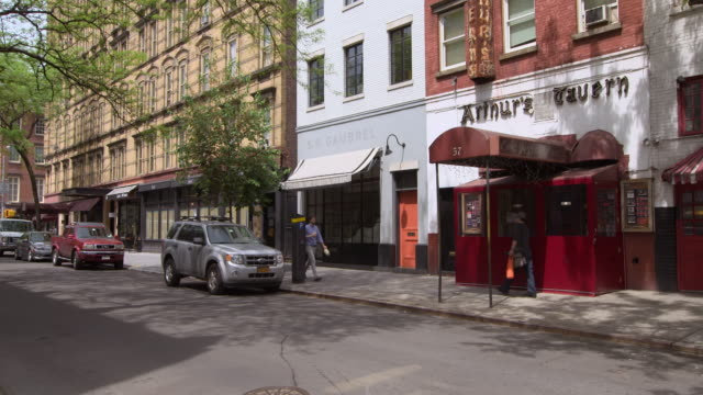 shot of the exterior of authur's tavern in the west village in downtown manhattan. people walk by on the sidewalk - townhouse stock videos & royalty-free footage