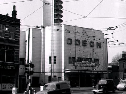 shot of the exterior of the odeon cinema in acton west london traffic moves along a road in the foreground 1960 - odeon kinos stock-videos und b-roll-filmmaterial