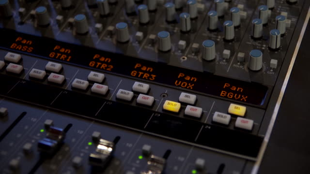 CU Shot Of The Flashing red CUT buttons of several tracks in a sound mixing desk stop flashing when a finger press the SOLO button / United States