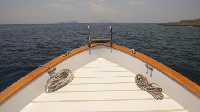 POV shot of the front of a recreational boat as it sails off the Sicilian coast, Italy.