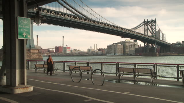 A shot of the Manhattan Bridge from underneath the FDR by the pedestrian walkway and man with a orange scarf crosses the frame.