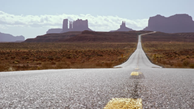 shot of the middle of a highway/interstate in the desert of arizona on a bright, sunny day with mountains and rock formations in the distance - monument valley stock videos & royalty-free footage