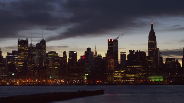 shot of the midtown manhattan skyline at night from across the hudson river. the empire state building, chrysler building, and new york times building  are all in the shot - dark stock videos & royalty-free footage