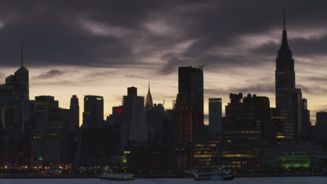shot of the midtown manhattan skyline at night from across the hudson river. the empire state building, chrysler building, and metlife building  are all in the shot - metlife hochhaus stock-videos und b-roll-filmmaterial