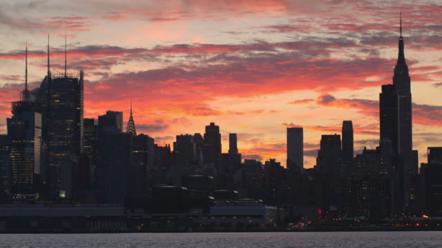 shot of the midtown manhattan skyline in the late afternoon.  the sky is lit up with oranges, pinks, and purples. the empire state building, chrysler building, and new york times building are visible. a ferry goes along the hudson river - stimmungsvoller himmel stock-videos und b-roll-filmmaterial