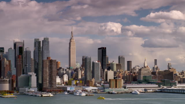 shot of the midtown manhattan skyline shot from across the hudson river. the empire state building,  new york times building, and the columbus towers are all in the shot. a water taxi goes down the river - water taxi stock videos & royalty-free footage
