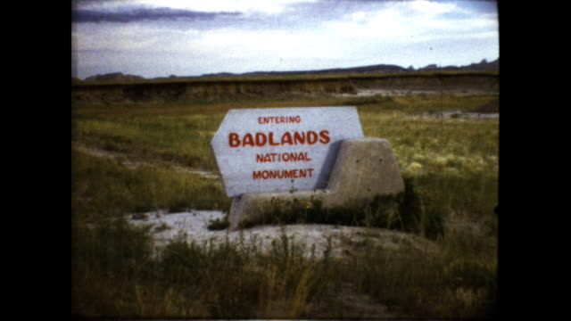 shot of the mount rushmore sculptures sign entering badlands national monument landscape shot of flat yellow field - バッドランズ国立公園点の映像素材/bロール