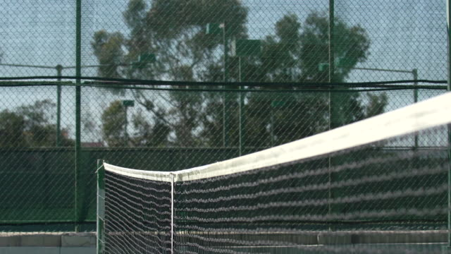 vídeos de stock, filmes e b-roll de shot of the net on a tennis court. - slow motion - quadra esportiva
