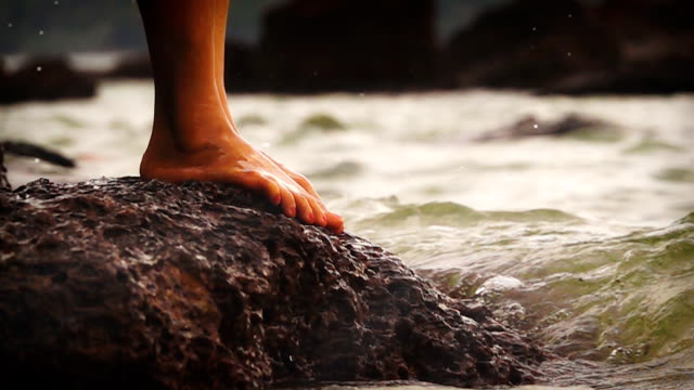 SLOW MOTION shot of the sea waves splashing against woman's feet while she standing on the rock.