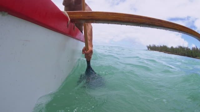 shot of the side of an outrigger as man paddles. - turtle bay hawaii stock videos & royalty-free footage