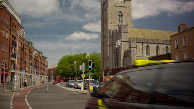 Shot of the steeple of a traditional Irish Catholic Church that tilts down reveal a busy city with people and cars passing by