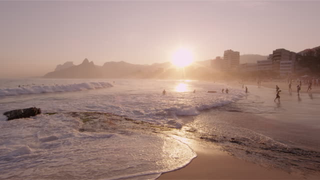 Shot of the sun about to set with people on the beach in Rio, Brazil.