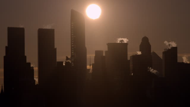 Shot of the sun rising on the Midtown Manhattan Skyline. The sky has a red hue.
