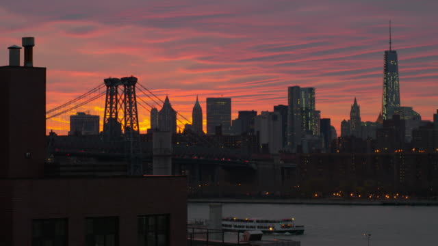 shot of the williamsburg bridge against the manhattan skyline.  one world trade center is clearly seen.  the sky and clouds are tinted orange and purple in the late afternoon sun. a boat comes down the east river - 気まぐれな空点の映像素材/bロール