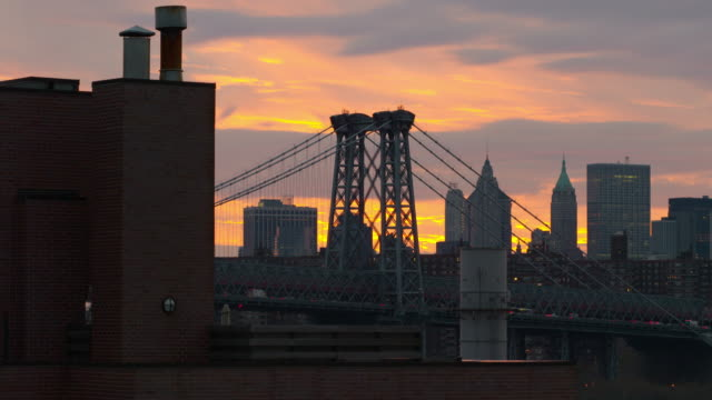 shot of the williamsburg bridge against the manhattan skyline.  the sky is colored yellow and purple in the late afternoon sun - stimmungsvoller himmel stock-videos und b-roll-filmmaterial