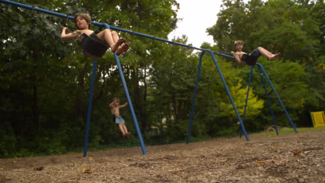 WS SLO MO Shot of three Caucasian male children on park swings, nearest one jumps off swing / Stanford, Connecticut, United States