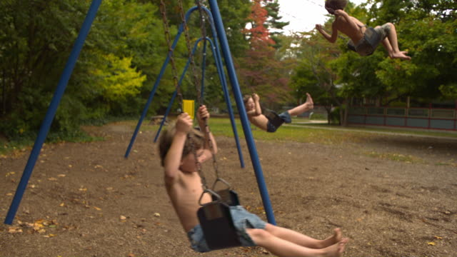 vídeos de stock, filmes e b-roll de ws slo mo shot of three caucasian male children on park swings, side view. nearest two to camera jump off, in slow motion / stanford, connecticut, united states - focus on foreground