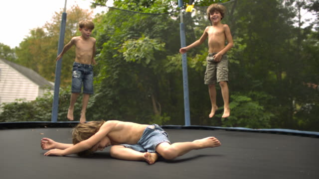 WS SLO MO shot of three Caucasian male children on trampoline with arms around each other, bouncing and falling / Stanford, Connecticut, United States