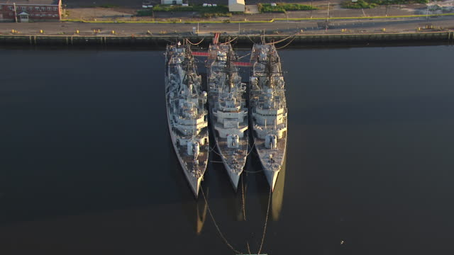 ms aerial shot of three navy destroyer ships docked at shipyard / philadelphia, pennsylvania, united states - bay of water stock-videos und b-roll-filmmaterial