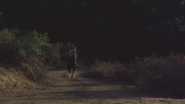 ms shot of three people on horseback moving on dirt road - 西方拡大点の映像素材/bロール