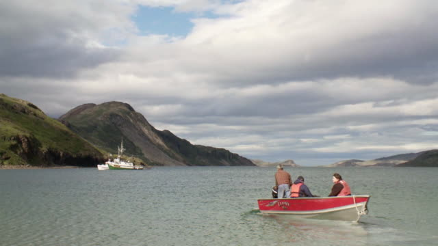 stockvideo's en b-roll-footage met ws shot of three people seating in small motor boat and moving towards anchor fishing boat / torgat mtns, labrador, canada - wiese