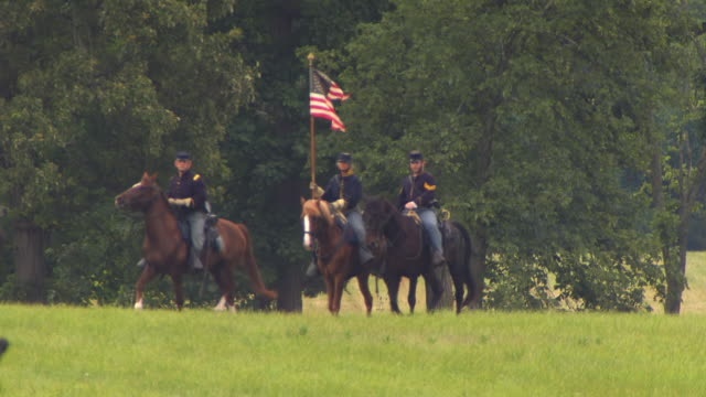 WS TS Shot of Three soldiers on horseback riding in Gettysburg carrying Round Pattern flag / Gettysburg, Virginia, United States