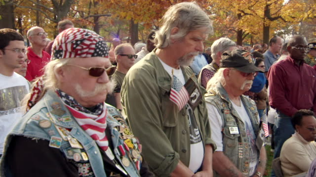 ms shot of three vietnam veterans with pow mia flags as they stand with heads bowing then lift their heads and place hats and caps on their heads during event at vietnam veterans memorial wall on veterans day - vietnam veterans memorial video stock e b–roll