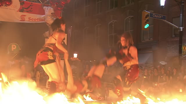 ms zo shot of three women performing acrobatics tricks inside ring of fire at busker fest / toronto, ontario, canada - street performer stock videos and b-roll footage
