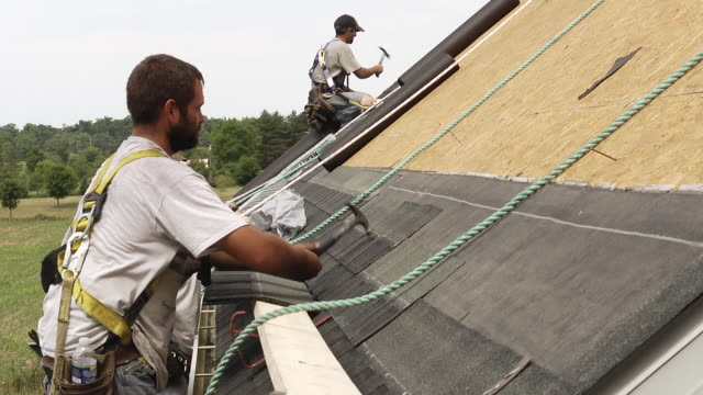 vidéos et rushes de ms shot of three workers hammering on roof of red building / chelsea, michigan, united states - couvreur