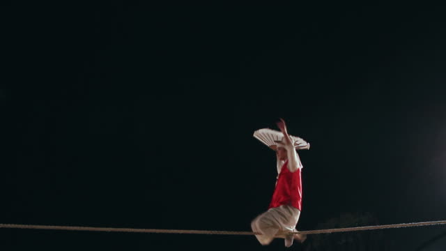 vídeos y material grabado en eventos de stock de ms shot of tightrope walker doing acrobatics on high wire at night / gyeonggido, south korea - alambre