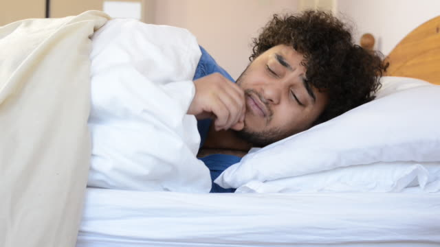 ms shot of tired man waking up in bed then going back to sleep / london, greater london, united kingdom - greater london video stock e b–roll