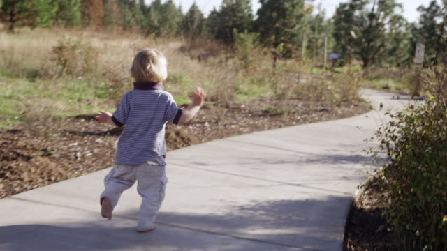 stockvideo's en b-roll-footage met ms ts slo mo shot of toddler baby running and toddles down concrete path on playground in sun / beaverton, oregon, united states - one baby boy only
