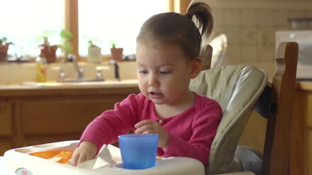 MS Shot of Toddler clean up her high chair tray with paper towel / Chelsea, Michigan, United States