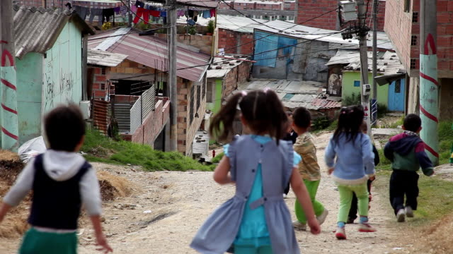 WS Shot of toddlers run and playing on dirt street in Ciudad Bolivar slum / Bogota, Colombia